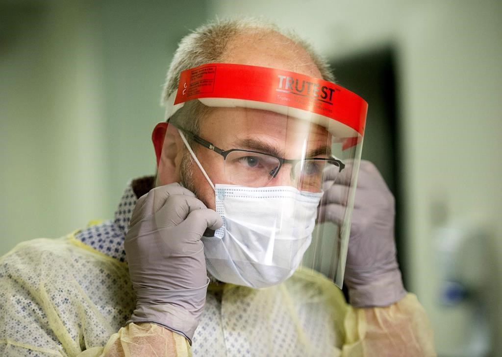 A man demonstrates how to put on a face mask and other protective clothing during a tour of a COVID-19 evaluation clinic in Montreal, Tuesday, March 10, 2020.