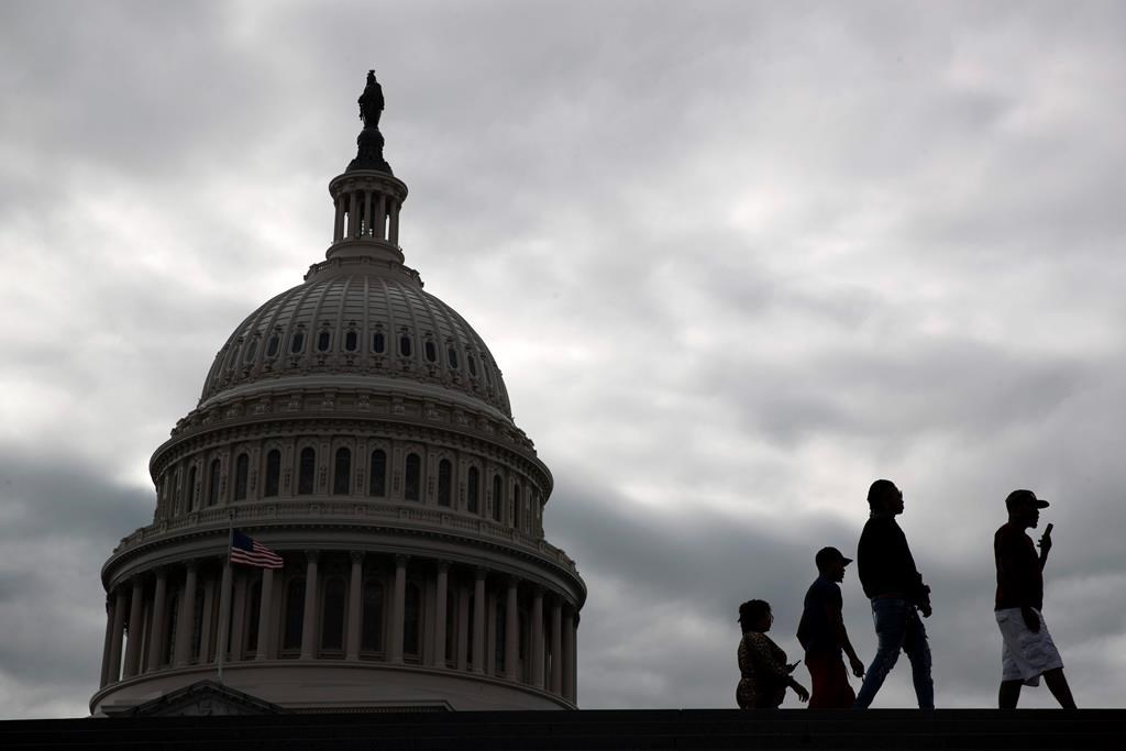 Visitors walk past the U.S. Capitol dome on Capitol Hill in Washington, March 12, 2020.