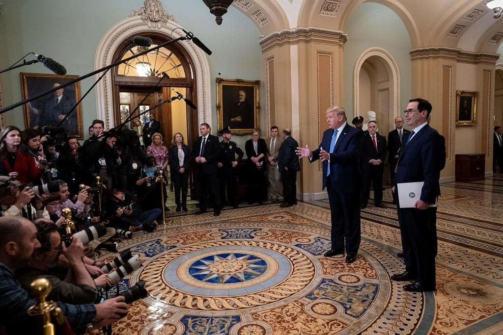 President Donald Trump, joined by Treasury Secretary Steven Mnuchin, right, speaks to reporters after meeting with Republican senators, on Capitol Hill in Washington, Tuesday, March 10, 2020. Trump wants Congress to pass payroll tax relief as he looks to calm financial markets' fears over the impact of the coronavirus epidemic. (AP Photo/J. Scott Applewhite).