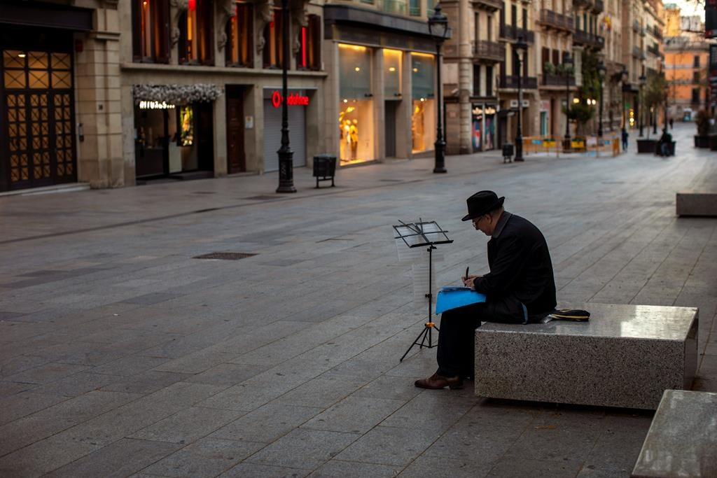 A man sits, in an empty street in Barcelona, Spain, Sunday, March 15, 2020. Spain's government announced Saturday that it is placing tight restrictions on movements and closing restaurants and other establishments in the nation of 46 million people as part of a two-week state of emergency to fight the sharp rise in coronavirus infections. For most people, the new coronavirus causes only mild or moderate symptoms. For some, it can cause more severe illness, especially in older adults and people with existing health problems.