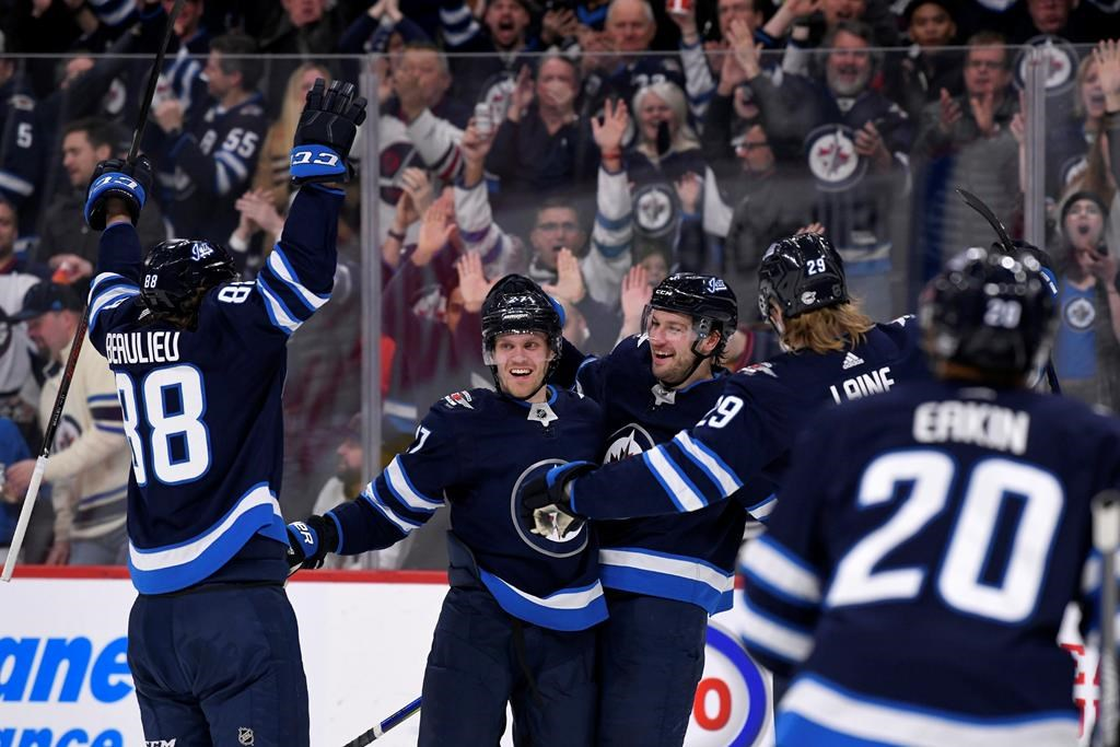 Winnipeg Jets' Tucker Poolman, centre, celebrates his goal against the Arizona Coyotes with teammates Nathan Beaulieu, left, Nikolaj Ehlers, second left, and Patrik Laine, second right, during second period NHL action in Winnipeg on Monday, Mar. 9, 2020. THE CANADIAN PRESS/Fred Greenslade.