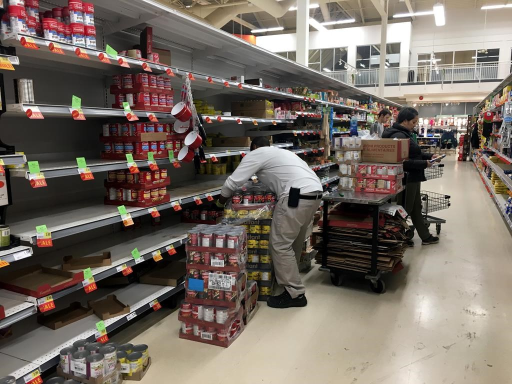Workers restock grocery store shelves with canned goods early in the morning in this file photo.