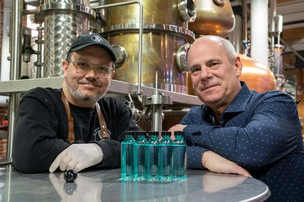 Spirit of York Head Distiller Mark Harrop (left) and founder Gerry Guitor pose with bottles of distillery-made hand sanitizer in Toronto on Wednesday March 18, 2020.