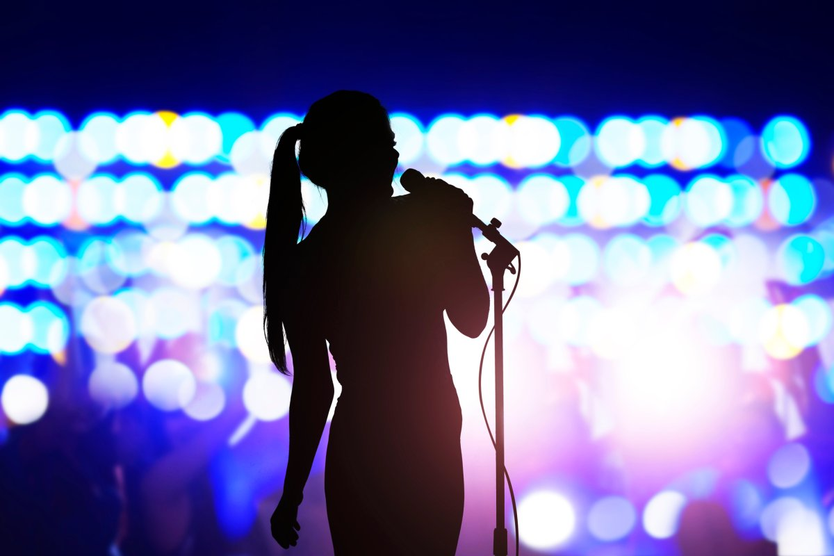 Silhouette of woman with microphone singing on concert stage in front of crowd.