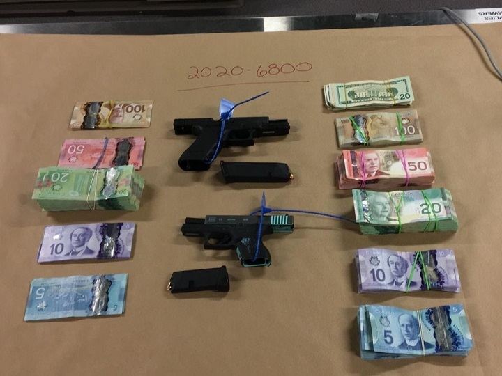 An RCMP photo showing two handguns plus Canadian and American currency that were seized during a search warrant in Kelowna last month.