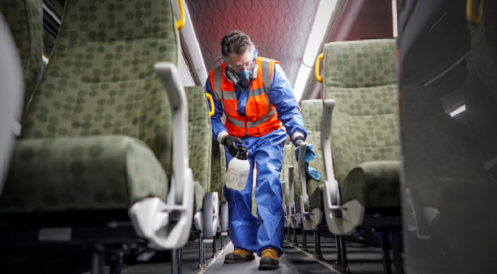 A GO bus is cleaned by a crew member in this handout photo.