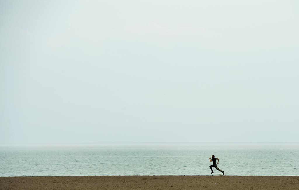 A lone man gets exercise at Woodbine Beach in Toronto on Thursday, March 26, 2020. CANADIAN PRESS/Nathan Denette.
