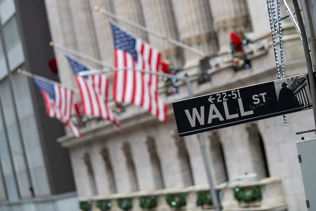 FILE - In this Jan. 3, 2020 file photo, the Wall St. street sign is framed by American flags flying outside the New York Stock Exchange in New York. (AP Photo/Mary Altaffer, File).