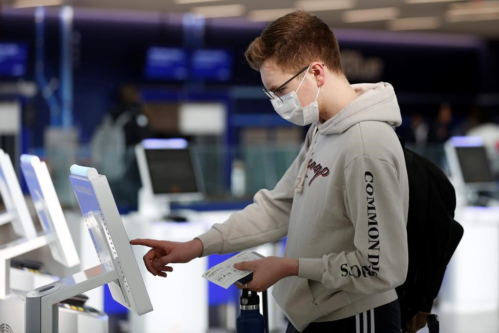 New York University student Hector Medrano, of Los Angeles, checks in for his flight using a touchscreen Saturday, March 14, 2020, at jetBlue's terminal in John F. Kennedy International Airport in New York. Medrano is traveling home during the school's spring break, and opted to wear a face mask as he travels to protect himself. (AP Photo/Kathy Willens).