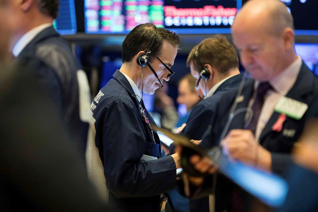 This photo provided by the New York Stock Exchange, Thursday, March 19, 2020, shows trader Gregory Rowe, center, as he works on the trading floor.
