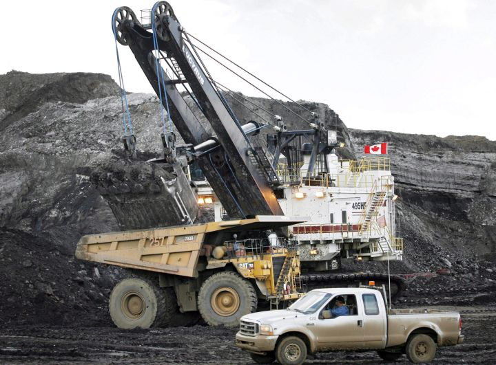 A pickup truck passes a mining shovel filling a haul truck at an oilsands mine near Fort McMurray, Alta., in this July 9, 2008 file photo. A million Canadians are asking the federal government to focus any bailout of the oil industry on workers and families, not corporations.
