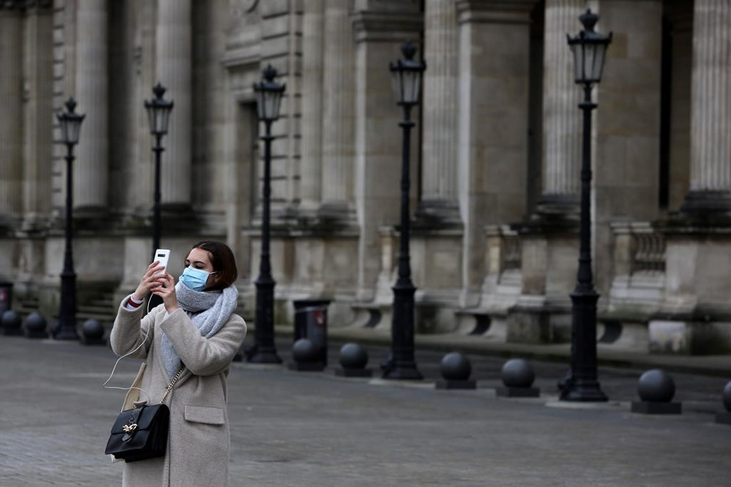 A tourist wearing a mask makes a selfie outside the Louvre museum Friday, Feb. 28, 2020 in Paris.