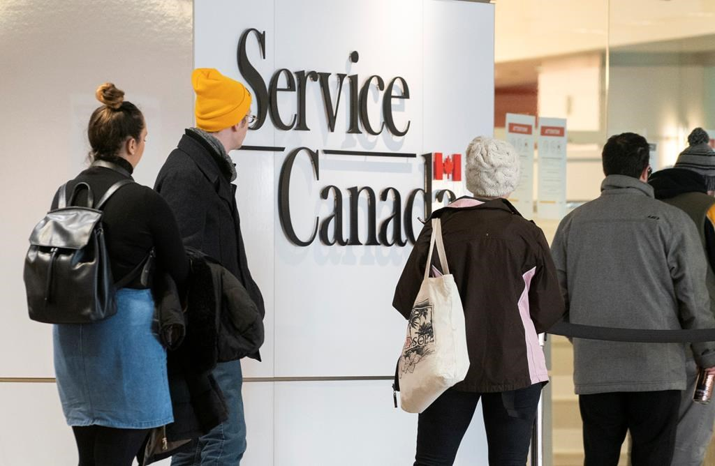 People line up at a Service Canada office in Montreal on Thursday, March 19, 2020. Canadians who have lost their jobs due to COVID-19 and are struggling to make ends meet anxiously awaited promised federal help with the Senate set to take up an emergency $82-billion financial package passed by the House of Commons on Wednesday.
