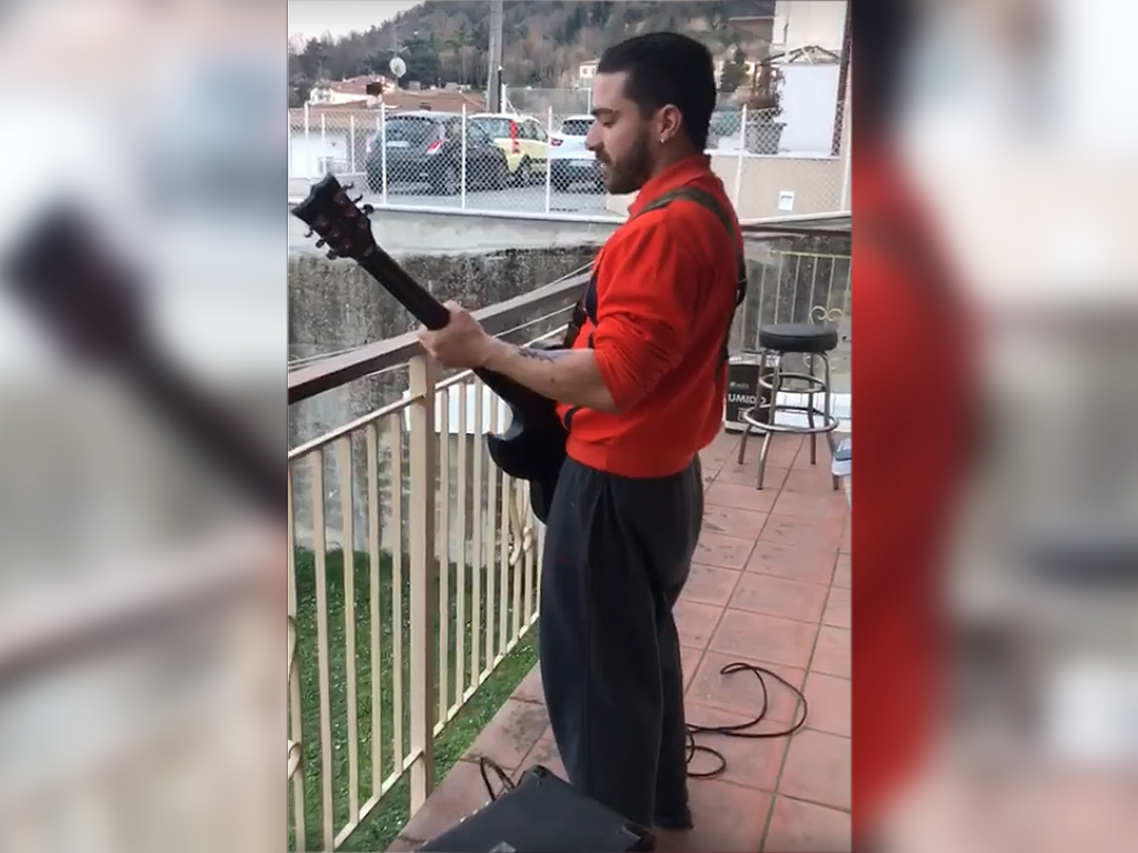 Enrico Monti, a quarantined Italian man, playing guitar on his balcony in Cesena, Italy on March 13, 2020, in the midst of the country's nationwide lockdown, during the COVID-19 outbreak.