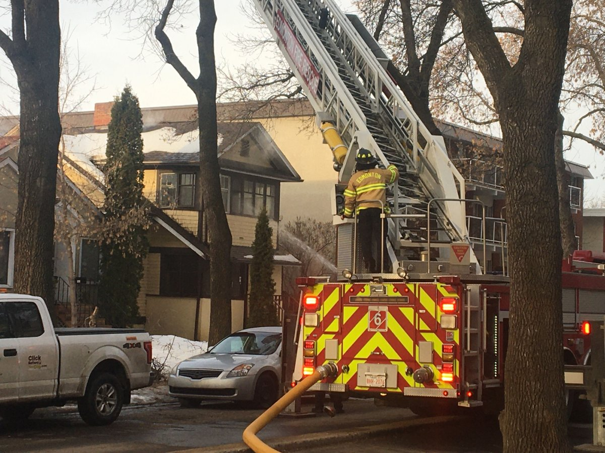 Fire crews battle a blaze at an unoccupied house on 83 Avenue between 100 and 101 streets Friday, March 27, 2020.