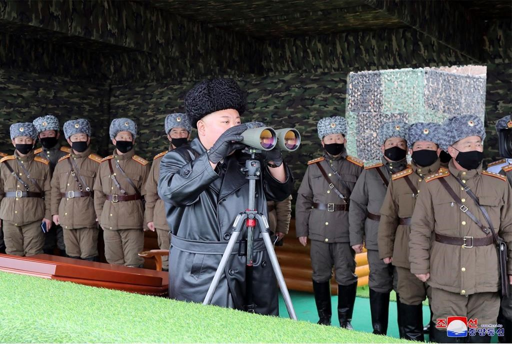 In this Friday, Feb. 28, 2020, file photo provided on Feb. 29, 2020 by the North Korean government, North Korean leader Kim Jong Un, center, inspects the military drill of units of the Korean People's Army, with soldiers shown wearing face masks. South Korea's military says North Korea has fired at least one unidentified projectile.