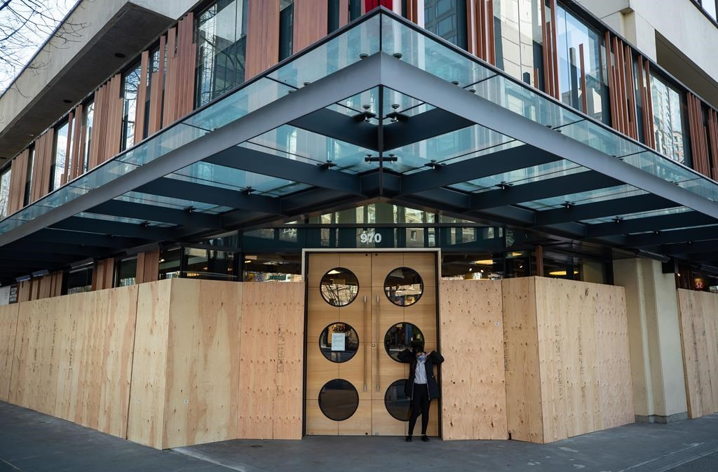 A Lululemon store with boarded up windows that has been closed due to the coronavirus, is seen in downtown Vancouver, on Wednesday, March 25, 2020.
