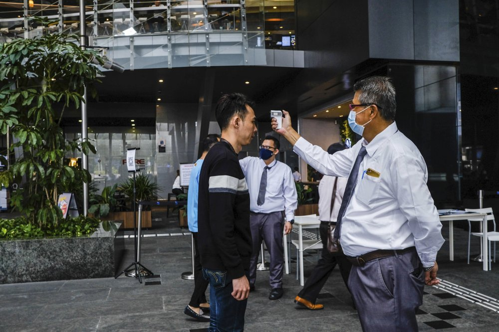 In this March 16, 2020, photo, a man scans a visitor's forehead to check his temperature before entering the Asia Square Tower in Singapore. As the virus outbreak spreads ever further, it's becoming clear that some strategies are more likely to succeed in containing it: pro-active efforts to track down and isolate cases, access to basic, affordable public health and clear, reassuring messaging from leaders. (AP Photo/Ee Ming Toh) .