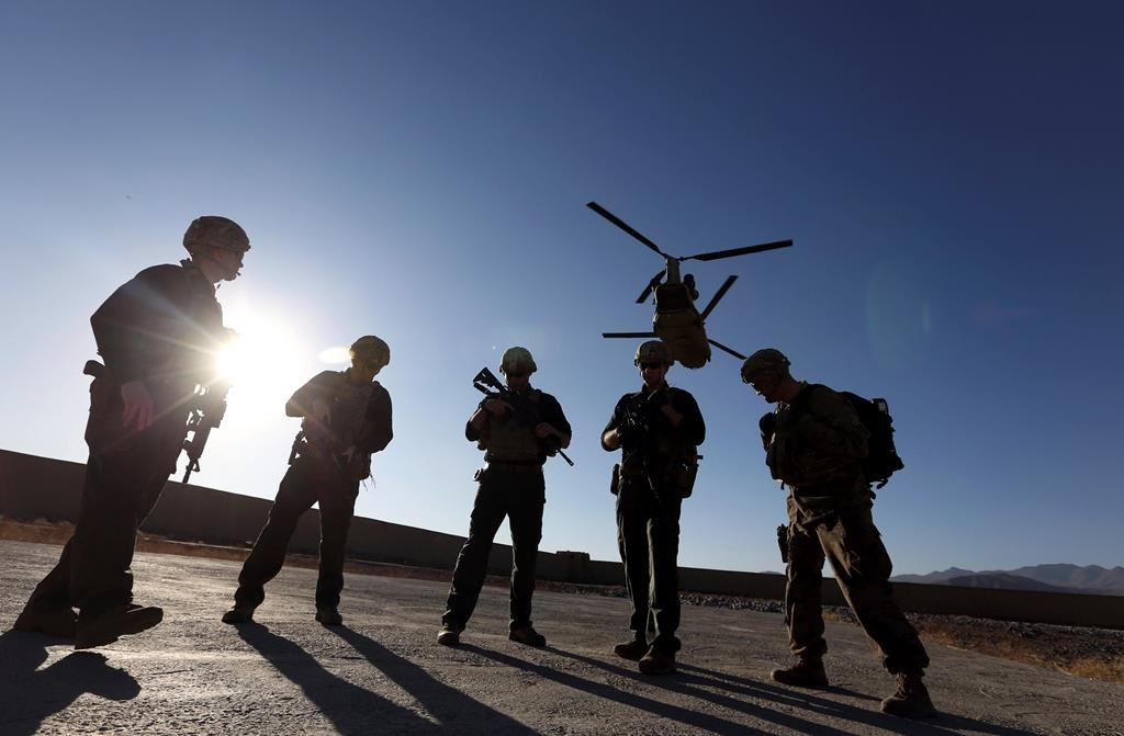 FILE - In this Nov. 30, 2017 file photo, American soldiers wait on the tarmac in Logar province, Afghanistan.