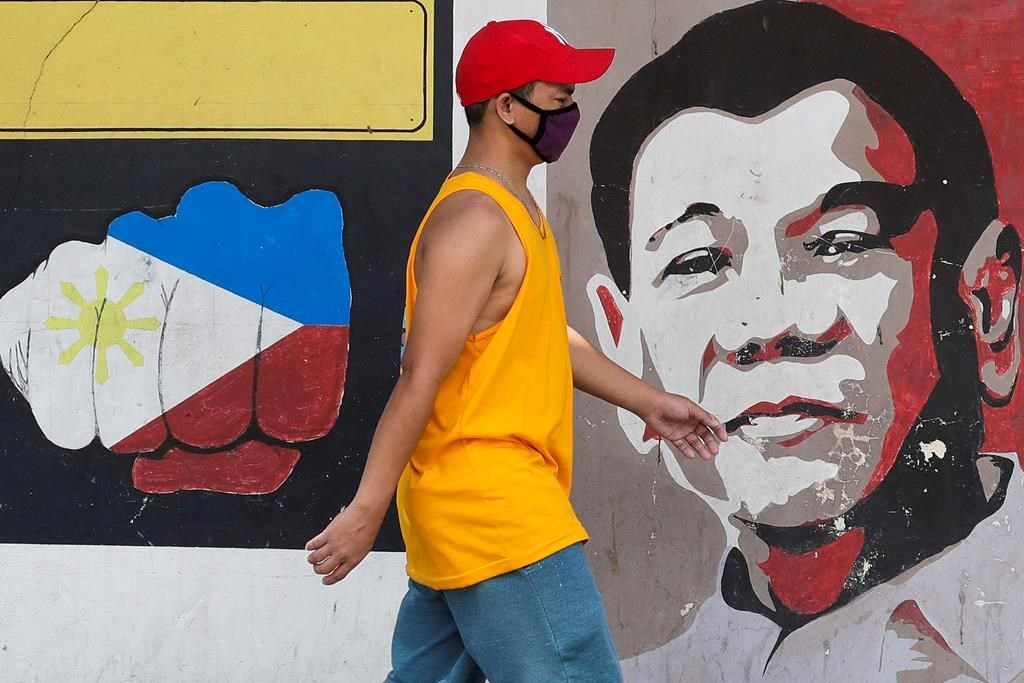 A man wearing a protective mask walks past an image of Philippine President Rodrigo Duterte in Manila, Philippines on Friday March 20, 2020.
