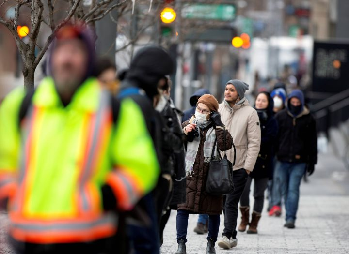 A woman adjusts her mask while she waits in line as the city's public health unit holds a walk-in clinic testing for coronavirus disease (COVID-19) in Montreal, March 23, 2020.