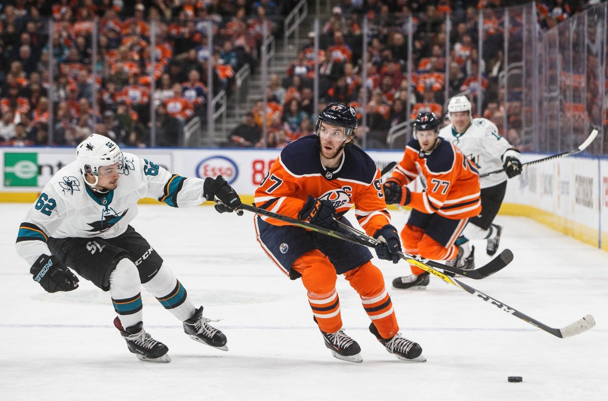 San Jose Sharks' Kevin Labanc (62) chases Edmonton Oilers' Connor McDavid (97) during second period NHL action in Edmonton, Thursday, Feb. 6, 2020. THE CANADIAN PRESS/Jason Franson.
