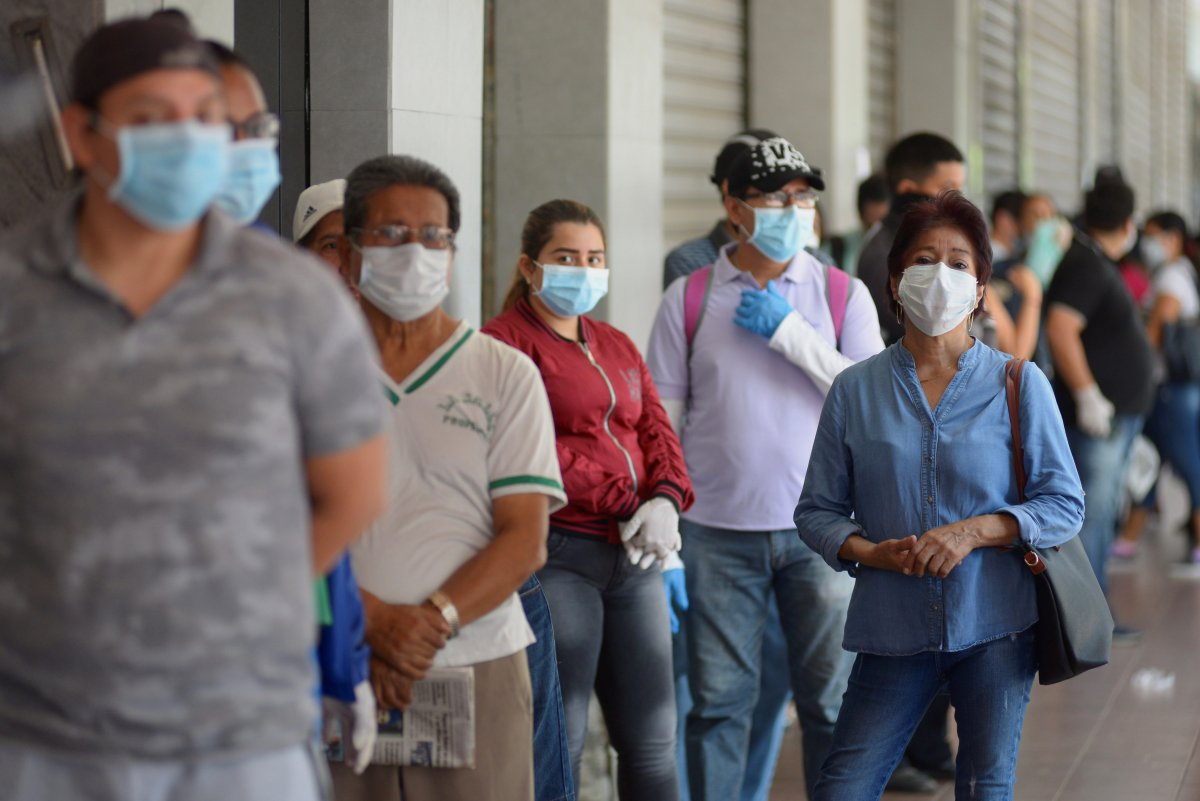 Citizens with face masks line up at a supermarket in Guayaquil, Ecuador, 24 March 2020.