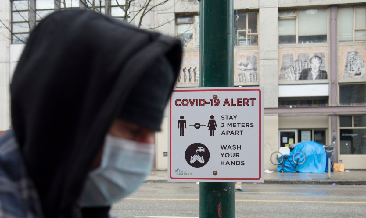 A man walks past a COVID-19 alert sign in Vancouver's downtown eastside Thursday, March 26, 2020. The large amount of homeless living on the streets in the DTES and lack of social distancing may result in a easy spread of COVID-19.