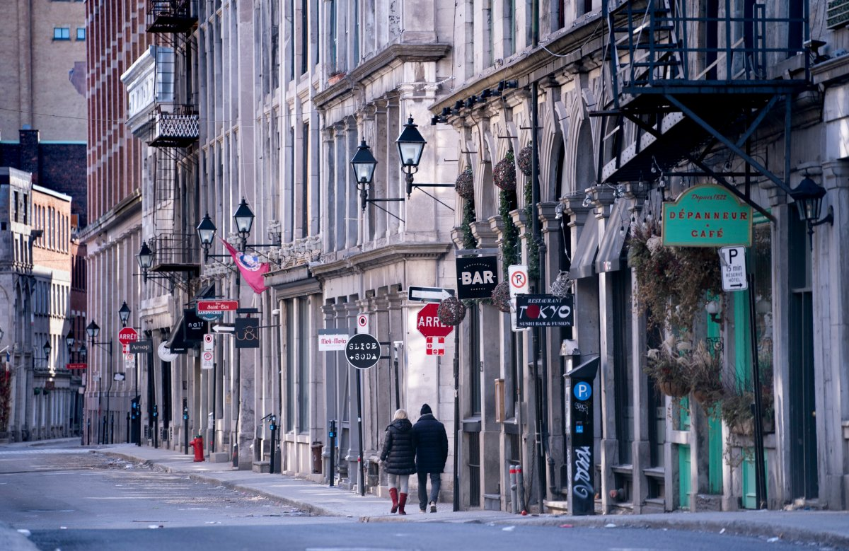 A couple walks along a deserted street in Old Montreal on Tuesday, March 31, 2020.
