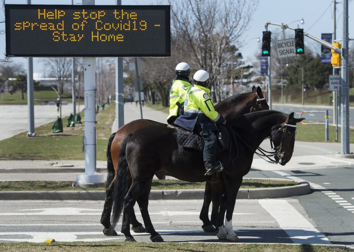 Toronto police officers stop at a red light as they patrol on their service horses in Toronto on Thursday, April 2, 2020.