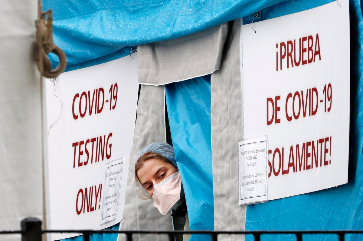 A medical worker sticks her head outside a COVID-19 testing tent set up outside Elmhurst Hospital Center in New York, Saturday, March 28, 2020. The hospital is caring for a high number of coronavirus patients in the city, and New York leads the nation in the number of cases, according to Johns Hopkins University, which is keeping a running tally. (AP Photo/Kathy Willens).