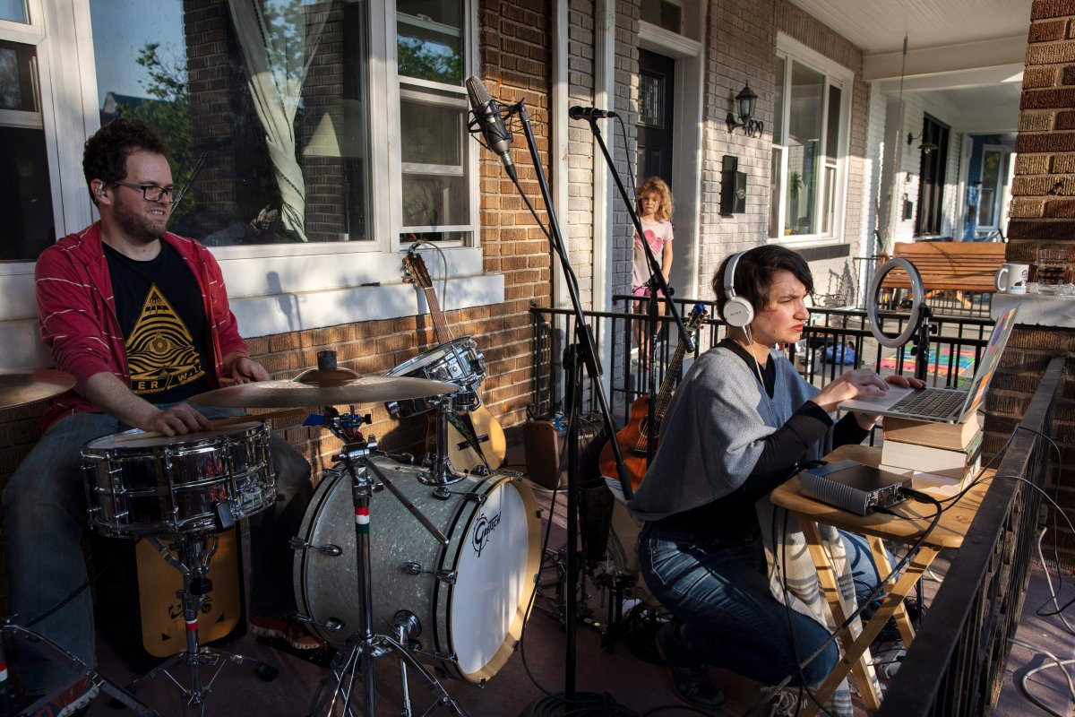 As neighbor Carys Williams, 7, peeks out of her house, drummer Andrew Northcutt, left, waits as singer Elena Lacayo, works on technical issues for their band, Elena and Los Fulanos, as they tried to live stream a concert from the porch of their house, Sunday April 5, 2020, in Washington. The band, who normally make their income from live concerts and touring, is trying to make some income under coronavirus restrictions by live streaming concerts and asking for contributions from their viewers.