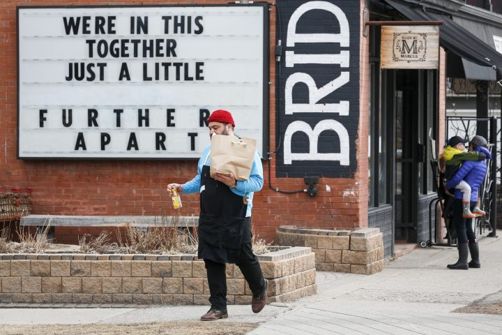 A grocery store clerk brings groceries to a waiting vehicle in Calgary, Alta., Thursday, April 9, 2020, amid the COVID-19 pandemic.