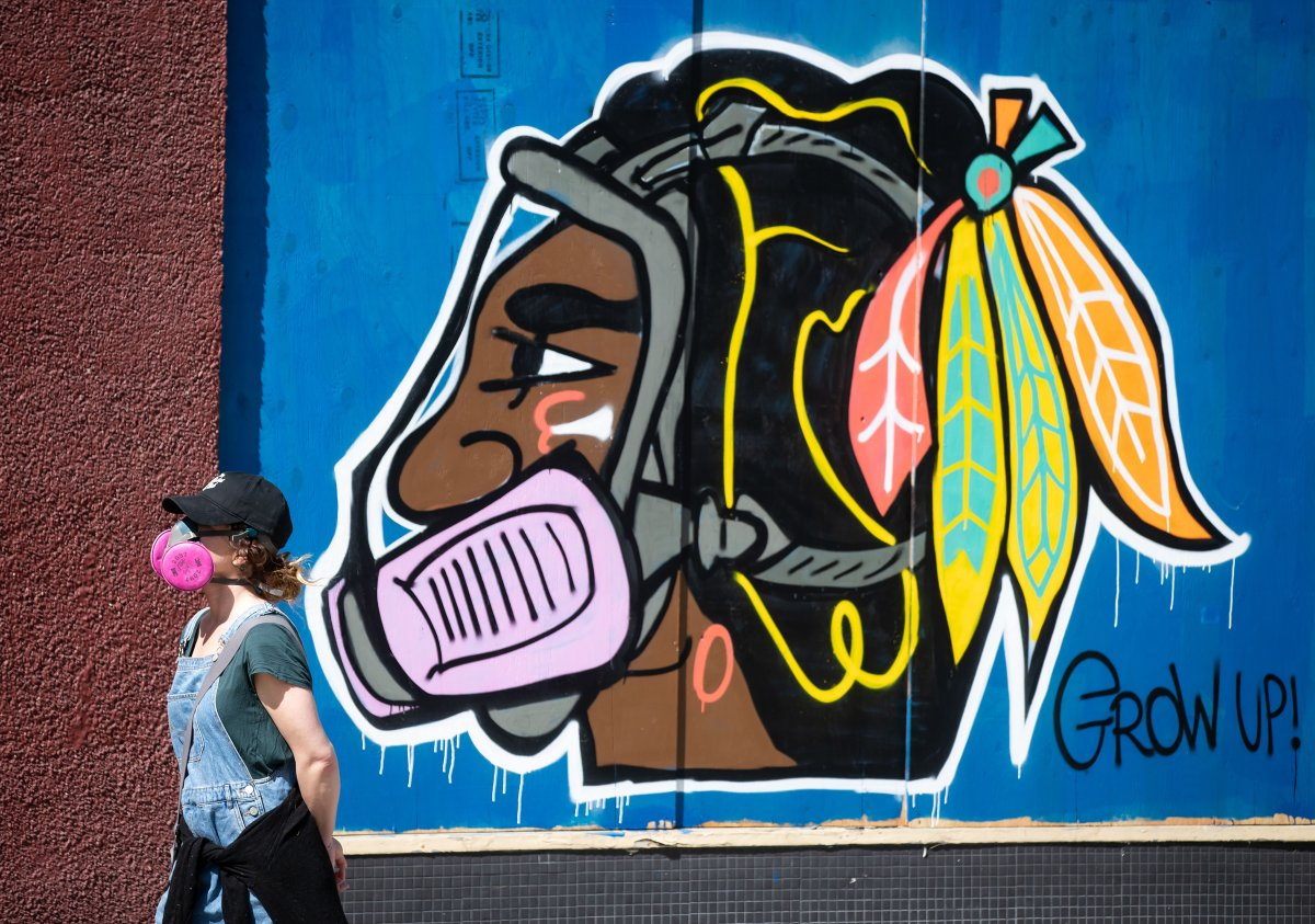 A woman wearing a P100 respirator, amid concerns about COVID-19, walks past artwork of the Chicago Blackhawks NHL hockey team's Native American chief logo wearing a respirator, in the Downtown Eastside of Vancouver, on Friday, April 10, 2020.