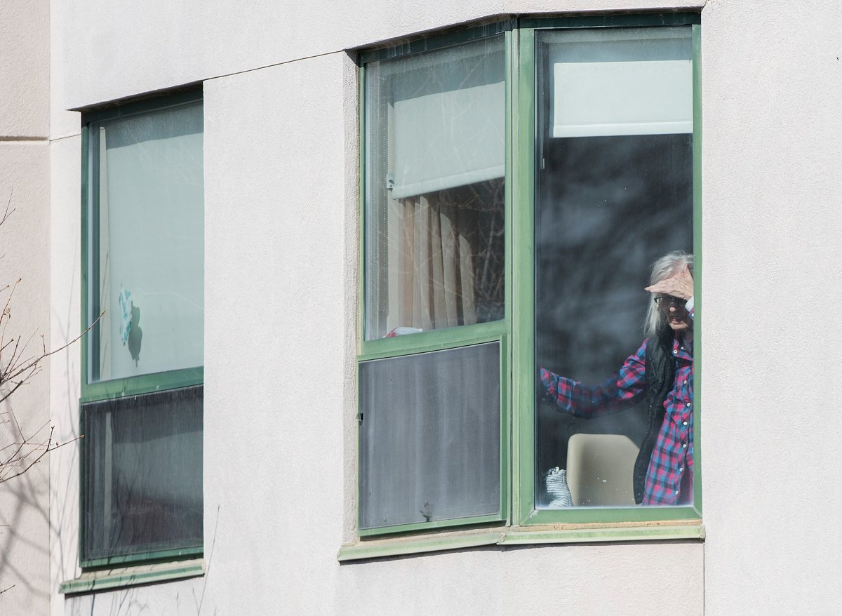 An elderly woman looks out of a window at Maison Herron, a long-term care home in the Montreal suburb of Dorval, Sunday, April 12, 2020, as COVID-19 cases rise in Canada and around the world.