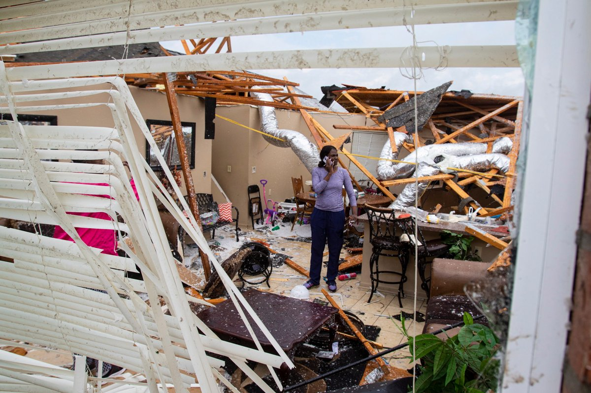 Rolanda Robinson calls family and friends from her brother's damaged home in Monroe, La. after a tornado ripped through the town on Sunday, April 12, 2020.