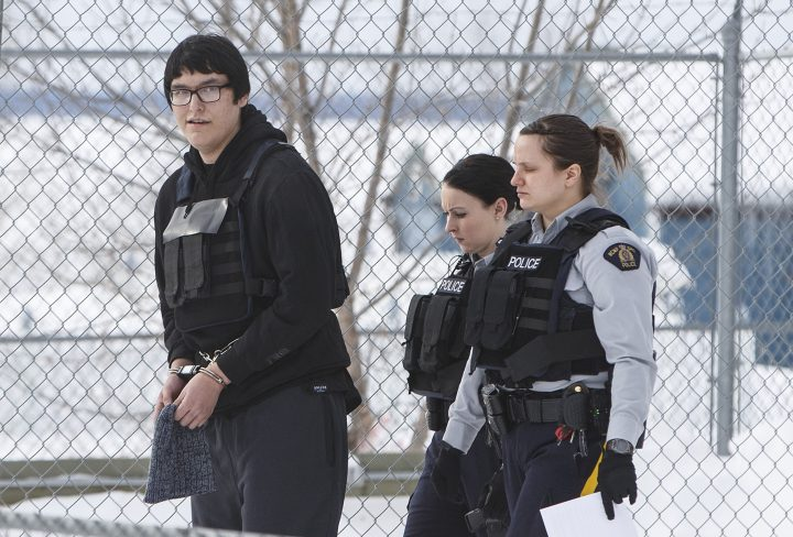 Randan Dakota Fontaine is led out of court in La Loche, Sask. on Friday, Feb.23, 2018 after a provincial court judge decided that he would be sentenced as an adult in the 2016 shooting spree that left four people dead and seven others wounded in La Loche.