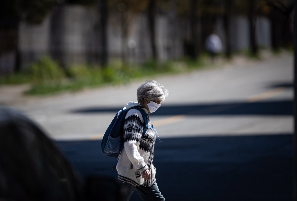 FILE - A woman wearing a fabric mask on her face walks in downtown Vancouver, on Thursday, April 16, 2020.