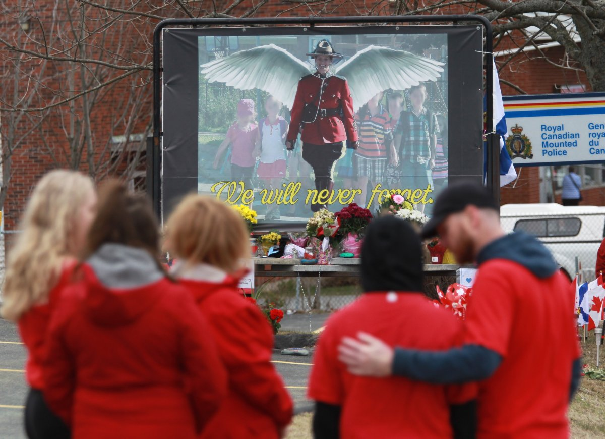Mourners, asked to wear red on Friday, are seen near a mural dedicated to slain RCMP Const. Heidi Stevenson, during a province-wide, two-minutes of silence for the 22 victims of last weekend's shooting rampage, in front of the RCMP detachment in Cole Harbour, N.S., Friday, April 24, 2020. THE CANADIAN PRESS/Tim Krochak.