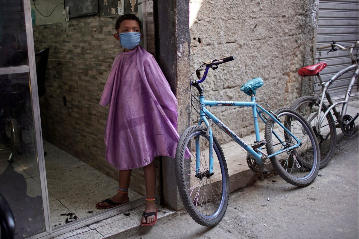 A boy wearing a protective face mask as a precaution against the COVID-19 coronavirus waits to get his haircut while standing in a doorway of a barbershop in the Mandela slum of Rio de Janeiro, Brazil, Tuesday, April 21, 2020.