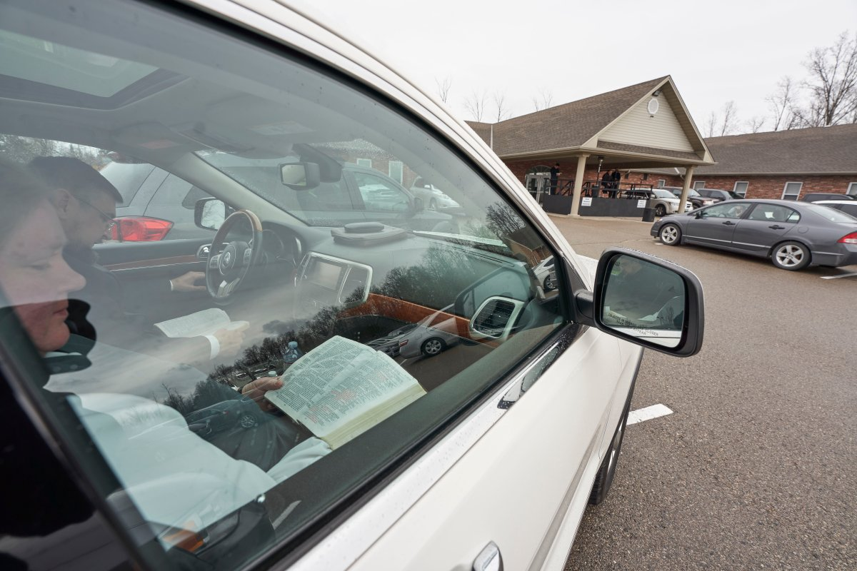 Parishioners read from the bible in their vehicles in the parking lot at The Church of God in Aylmer, Ont., on Sunday, April 26, 2020.