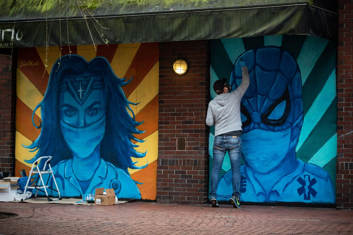 Artist Lukas Lundberg touches up a painting of Spiderman depicted as a paramedic while working on a painting of Wonder Woman as a doctor, on the boarded up windows of a closed Gastown business, in Vancouver, on Sunday, April 26, 2020.