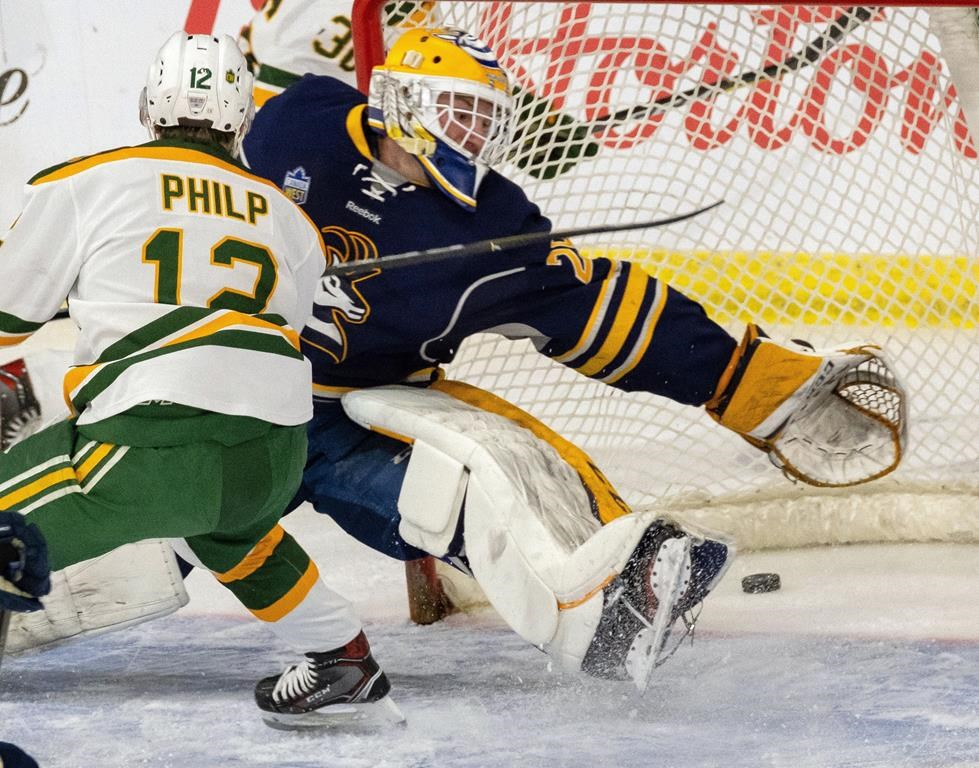 University of Alberta Golden Bears' Luke Philip slides the puck past University of Lethbridge Pronhorns goaltender Garret Hughson during U CUP hockey action Thursday, March 14, 2019, in Lethbridge, Alberta. The University of Lethbridge has shut down its men's and women's hockey teams citing three straight years of cuts to its operating grant. THE CANADIAN PRESS/David Rossiter.