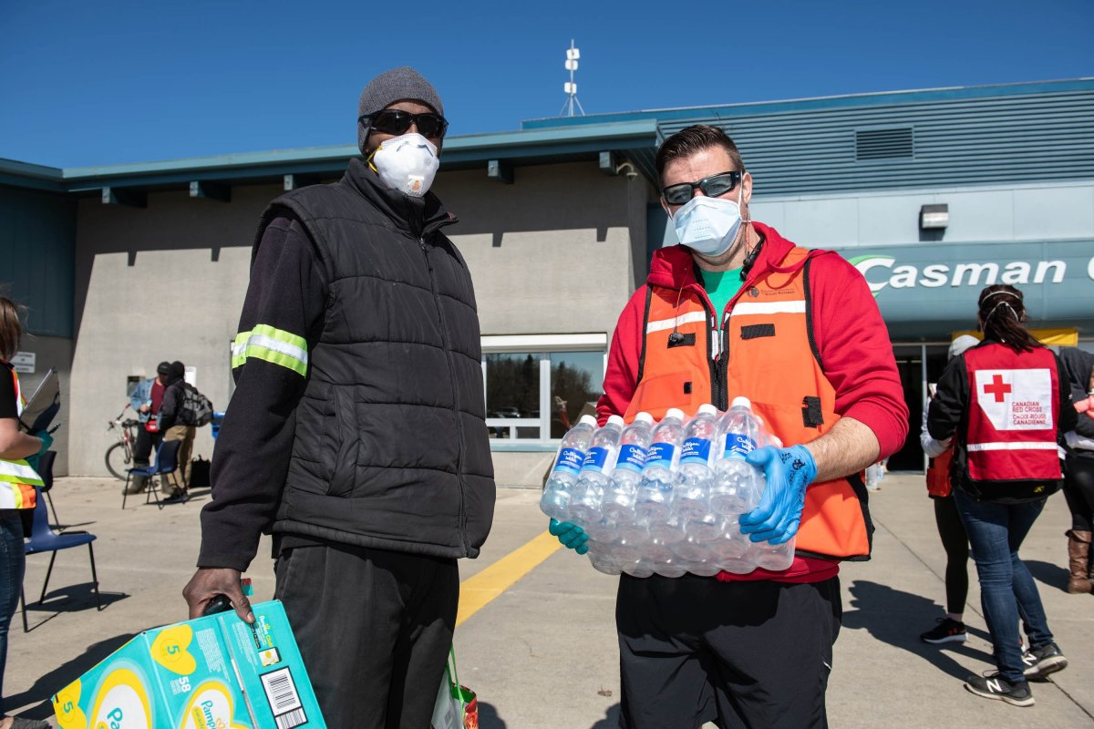 A Red Cross volunteer supplies water and diapers to flood evacuee Abdigani Abokar (left) at an evacuee registration centre at an ice arena in the Thickwood Heights neighbourhood of Fort McMurray, Alta. on Tuesday, April 28, 2020. A boil water advisory in Fort McMurray could be lifted sooner than originally anticipated.