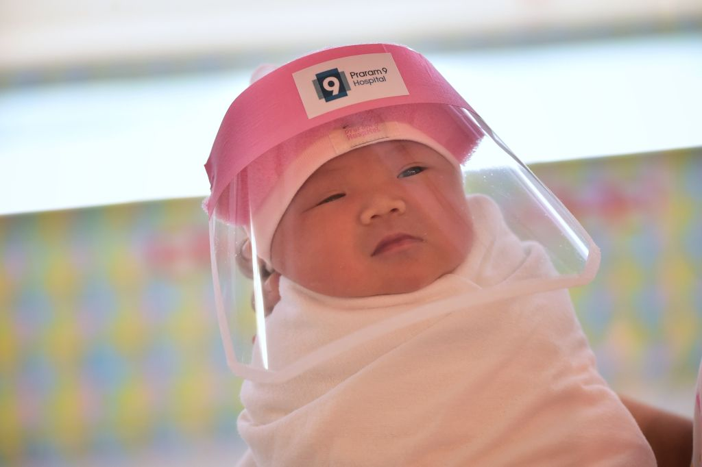 This photo taken through a glass window at a maternity ward shows a newborn baby wearing a face shield in an effort to halt the spread of the COVID-19 coronavirus at Praram 9 Hospital in Bangkok, Thailand on April 9, 2020.