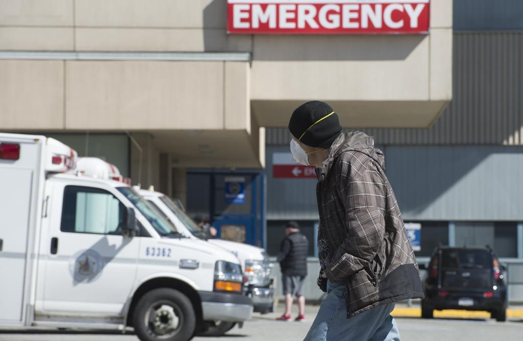 A man wears a protective face mask as he walks past the emergency department of the Royal Columbian Hospital in New Westminster, B.C. Friday, April 3, 2020. Health-care providers are warning of an unseen toll COVID-19 could take if people die because they are too afraid to go to an emergency room for serious health issues unrelated to the pandemic. THE CANADIAN PRESS/Jonathan Hayward.