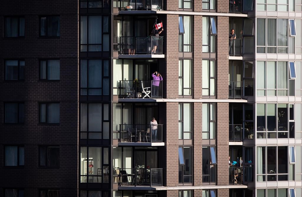 A man waves a flag as others applaud and make noise on condo balconies during the nightly 7 p.m. salute to health-care workers, in Vancouver, on Friday, April 10, 2020.