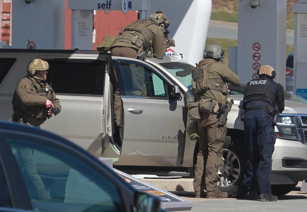 RCMP officers prepare to take a person into custody at a gas station in Enfield, N.S. on Sunday April 19, 2020.