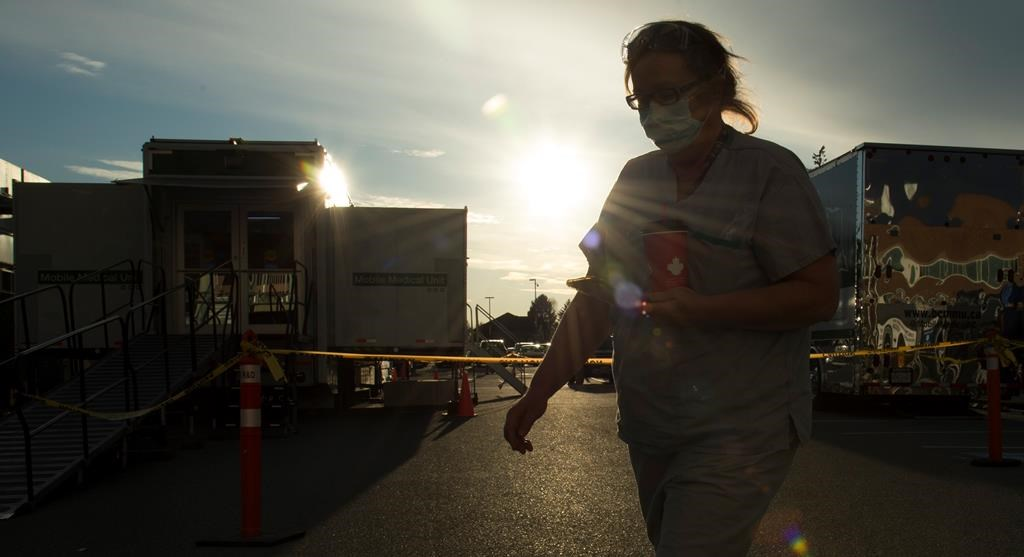 A health-care worker is silhouetted as they walk past the British Columbia mobile medical unit set up outside of Abbotsford Regional Hospital in Abbotsford, B.C. Tuesday, April 14, 2020. The mobile medical unit was deployed to Abbotsford to assist with the COVID-19 outbreak that has occurred at the Mission Correctional Institution.