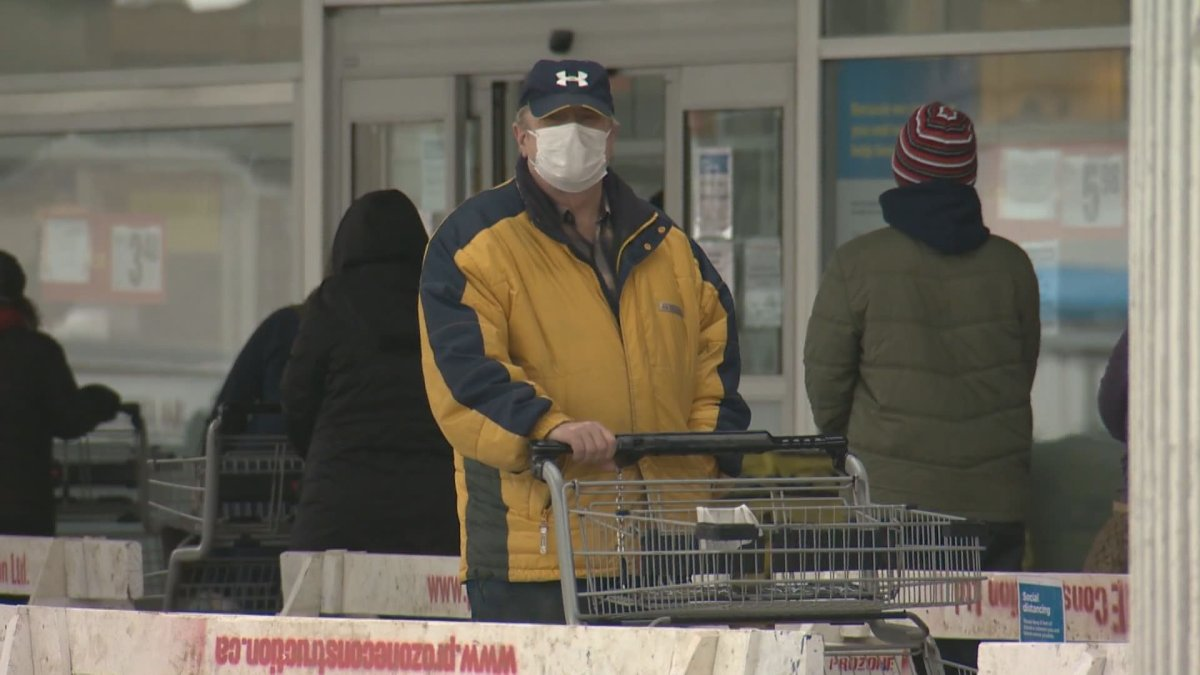 Man stands in a lineup to be let into an Edmonton grocery store amid the COVID-19 pandemic.